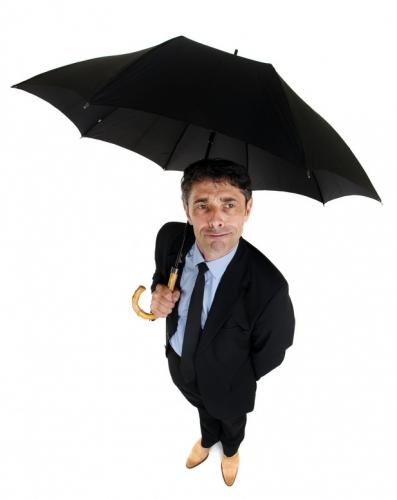 fotolia_58279629_stephane_bidouze_dapper_businessman_sheltering_under_an_umbrella_s.jpg